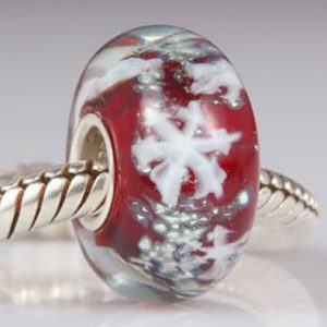 a red glass bead with snowflakes